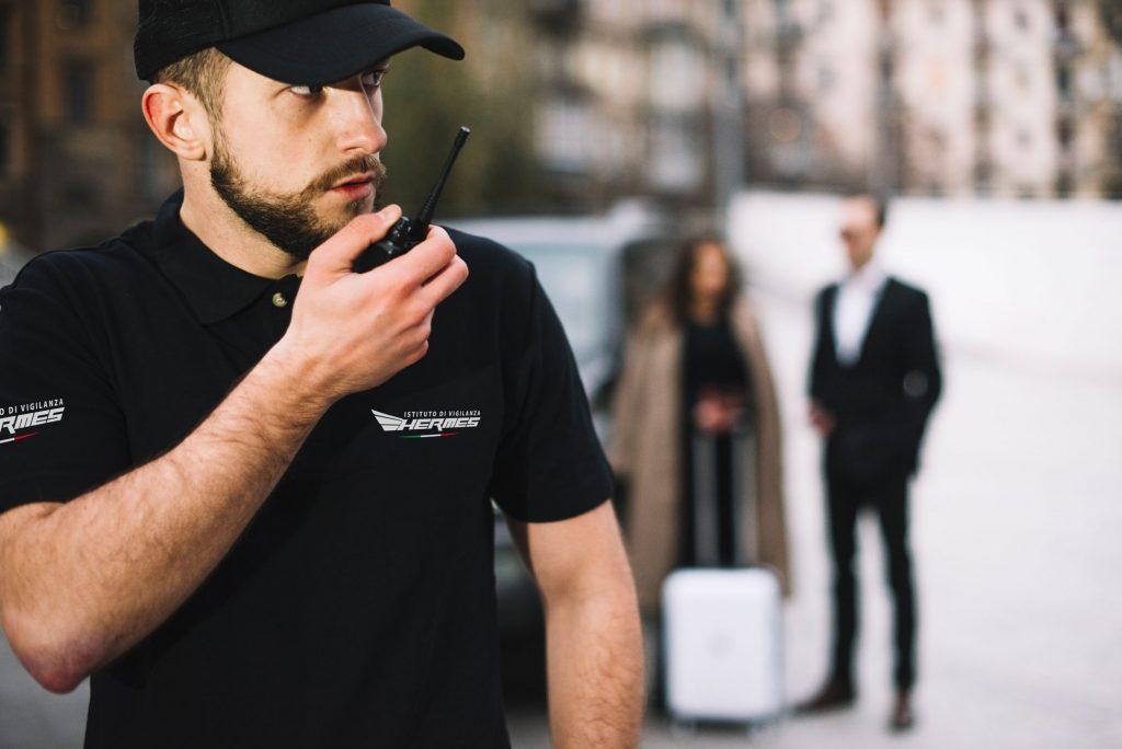 Uomo della sicurezza vigilanza hermes parla al walkie talkie